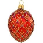 Shimmering in a vivid hue of ruby red with eye-catching accents, this stunning hand-painted ornament was inspired by the famous jeweled eggs of the House of Faberge, in St. Petersburg, Russia. A sparkling gold glitter diamond pattern with purple and