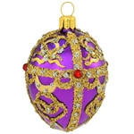 An egg-ceptional choice for the tree, this dazzling glass ornament was inspired by the famous jeweled eggs of the House of Faberge, in St. Petersburg, Russia. Featuring sparkling glitter folk patterns and glistening gold lines studded with eye-catching