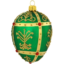 Shimmering in a bright hue of emerald green, this stunning glass ornament was inspired by the famous jeweled eggs of the House of Faberge, in St. Petersburg, Russia. Featuring dazzling gold glitter folk patterns surrounded by metallic gold lines studded