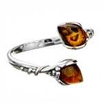 "Sterling silver open ring highlighting two amber cabochons. Size is approx .5"" x .25"""