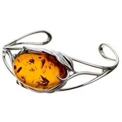 "This sterling silver bracelet features a gorgeous honey amber cabochon.. Bracelet size is 7"" diameter. Cabochon size is approx 1"" x 1.25""."