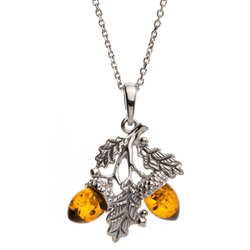 "Sterling silver oak leaves hold two honey amber acorns. Pendant size is approx. 1"" h x .75"" w."