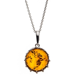 "A sterling silver crown is the frame for this beautiful round honey amber cabochon.  Pendant size is approx. 1"" x .75""."