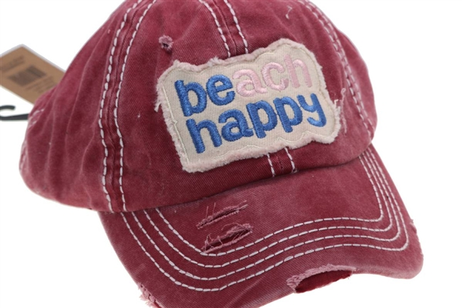 Maroon ponytail cap says, beach happy.
