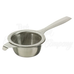 Tea strainer has a long handle with a drip tray