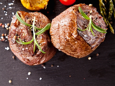 Cooked filet mignon with sprigs of fresh rosemary