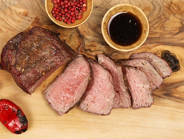 Sliced medium-rare prime sirloin next to a saucer of steak sauce.