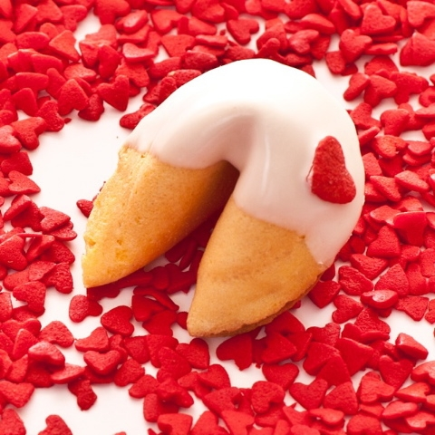traditional vanilla fortune cookies covered in chocolate with pink and white heart candy sprinkles each