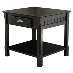 A small end table made of solid wood that features a lower shelf and a pull out drawer with a brushed silver handle.