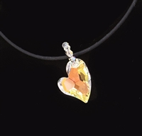 Devoted 2 U Heart Crystalized with Swarovski hangs on a bias. The Classic Aurora Borealis coating shines a warm yellow to hot orange when worn on a dark color.