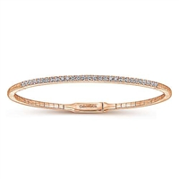 This diamond bangle bracelet in 14k rose gold boasts over one half carats of round brilliant diamonds that stand out over 14k rose gold.
