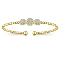 This 14k yellow gold cuff style bangle bracelet features one third carats of diamond shine.
