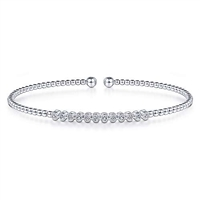 Round brilliant diamonds shimmer in this 14k white gold bezel set diamond cuff bangle style bracelet.