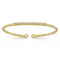 12 round diamonds align in this 14k yellow gold diamond cuff bracelet.