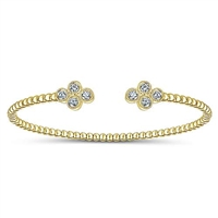 This simple cuff features a thin band of 14k yellow gold with diamonds centered in a cluster settings.