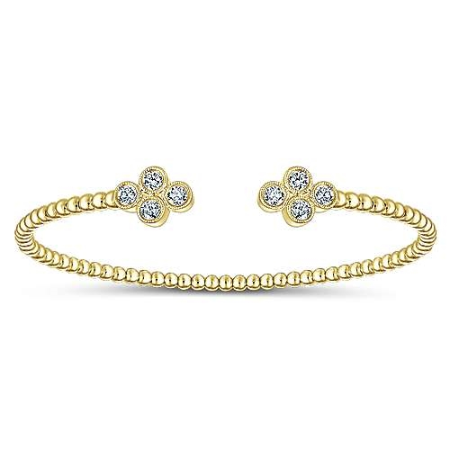 daaa76c2be2 This simple cuff features a thin band of 14k yellow gold with diamonds  centered in a