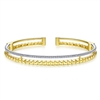 This 14k two tone cuff bangle features one half carats of diamonds.