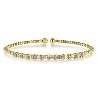 11 Round brilliant diamonds glisten in this 14k yellow gold beaded bangle bracelet.