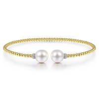 This 14k yellow gold bangle features pearls and diamonds.