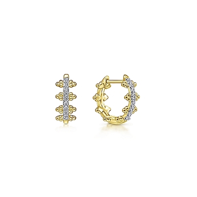 These 14k yellow gold diamond huggie earrings feature 0.10 carats of diamonds.