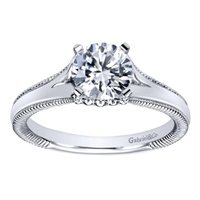 This split shank solitaire engagement ring with a touch of metalwork on the sides shows off a round center diamond of your choice! Available in white gold or platinum.