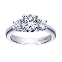 Two round brilliant diamonds anchor a round center diamond of your choice in this contemporary 3 stone engagement ring in white gold or platinum.