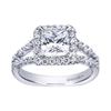 One half carats of round brilliant diamonds amass at the center of this split shank engagement ring, forming the round brilliant diamond halo that cradles a princess cut center diamond of your choice.