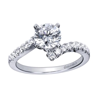 A single diamond row swirls towards a round center diamond in this sleek and stylish white gold or platinum diamond engagement ring.