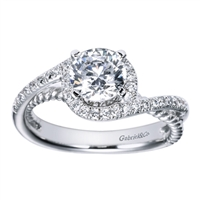 A round center diamond sits warm and cozy in the middle of white gold or platinum bands covered in round brilliant diamonds in this contemporary bypass engagement ring.