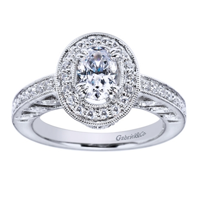 A vintage style halo engagement ring set with nearly one half carats in round brilliant diamonds fabulously decorates an oval shaped center diamond in this engagement ring available in white gold or platinum.