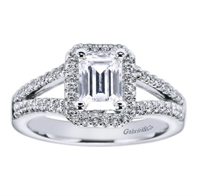 An emerald cut center diamond is shown off in the middle of this contemporary halo engagement ring available in white gold or platinum.