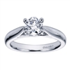 A sturdy, 4 prong setting in white gold or platinum shows off a round center diamond in this contemporary solitaire engagement ring.