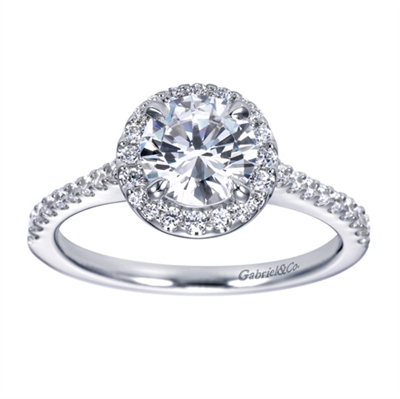 Round brilliant diamonds grace this contemporary halo engagement ring with shine, and the round halo at its center cushions and lifts a round center diamond of your choice.