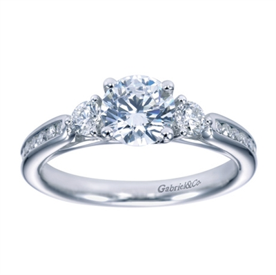 Set with brilliant round diamonds, this contemporary 3 stone engagement ring sparkles with radiance as it sits on her finger.