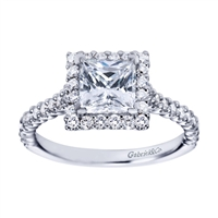 A princess cut center diamond is wrapped with round brilliant diamonds in this contemporary style princess engagement ring available in white gold or platinum.
