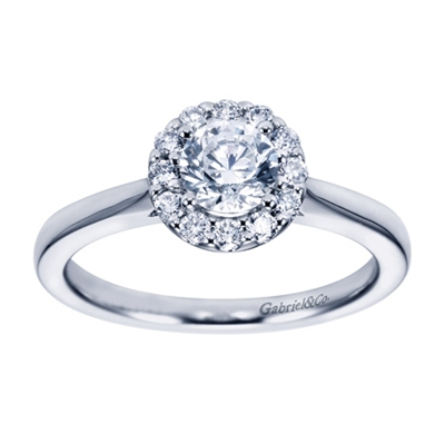 A round brilliant halo contrasts perfectly with the sleek white gold band in this contemporary halo engagement ring available in platinum or white gold.
