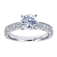 A round center diamond sits perfectly in a vintage inspired straight engagement ring with side round brilliant diamonds.