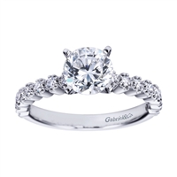 Round prong set brilliant diamonds lift this contemporary straight engagement ring designed by Gabriel & Co.