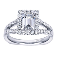 This split shank halo engagement ring perfectly houses an emerald cut center diamond with nearly one half carats of round brilliant diamonds.