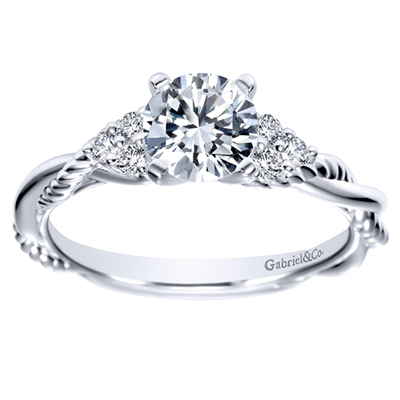 This sleek criss cross diamond engagement ring wraps around itself as white gold or platinum bands make their way up to a round center diamond in this contemporary diamond engagement ring.