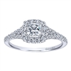 A center princess cut diamond sits snugly in a round diamond halo with a split shank setting in this clever 14k white gold diamond halo engagement ring.