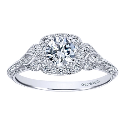 This vintage style diamond engagement ring showcases a decorated halo with an included round center diamond flashing brilliantly in the middle of this artistic diamond engagement ring.