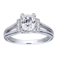 This split shank diamond engagement ring is in a solitaire style with the round diamonds assembling at the center, surrounding the oval cut diamond of your choice.