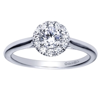 A sleek white gold band leads up to a round diamond halo engagement ring with a round center diamond already included!