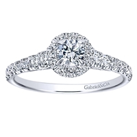 Round brilliant diamonds shine their way up towards a round diamond halo, all capped off with an included round center diamond, in this 14k white gold diamond halo engagement ring.