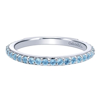 A row of blue topaz stones shine in this 14k white gold stackable ring.