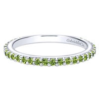 A row of peridot stones shimmer in this 14k white gold stackable ring.