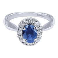 A 1 carat center sapphire shines brilliantly in a round diamond halo all set in 14k white gold in this engagement ring alternative.