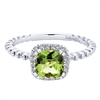 This delicate dandy features 14k white gold leading up to a peridot with a round diamond halo in this 14k white gold diamond gemstone ring.