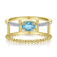 This uniquely styled 14k yellow gold diamond and blue topaz ring features beaded 14k yellow gold.